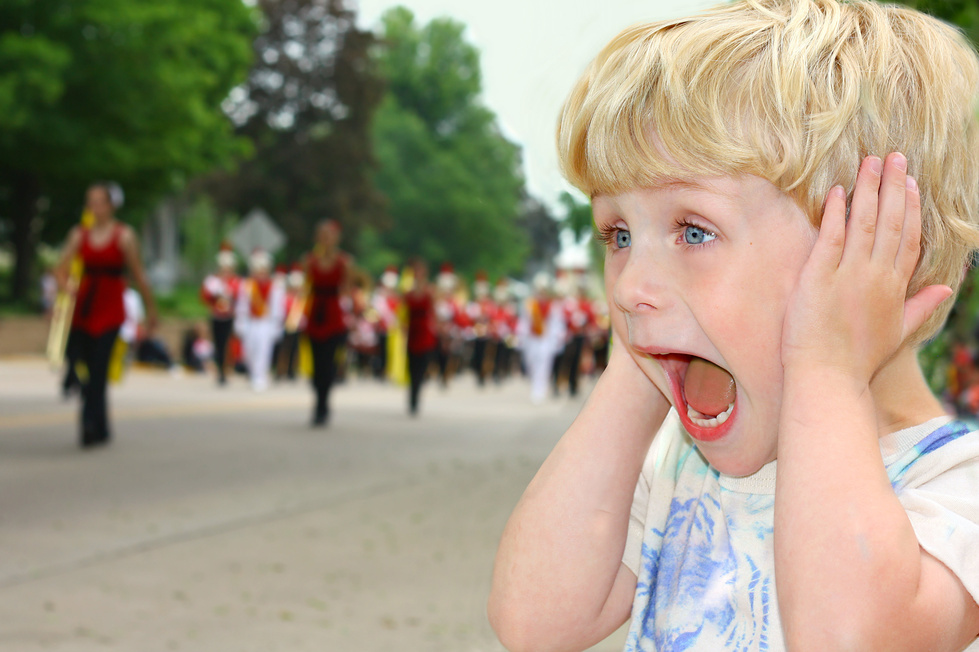 Child Covers Ears During Loud Parade
